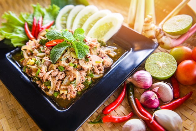Thailändisches lebensmittel des würzigen gehackten schweinefleischsalats diente auf tabelle mit kräutern und gewürzbestandteilen.