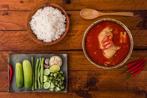 Thailändisches lebensmittel, hühnermiesamancurry in einer schüssel und reis auf holz