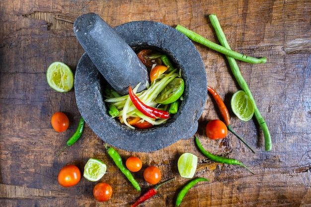 Thailändisches lebensmittel kochen, papayasalat und gewürz auf einem holztisch