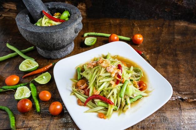 Thailändisches lebensmittel, papayasalat und papayasalat in einem teller mit einer umhüllung auf einem holztisch kochen. Premium Fotos