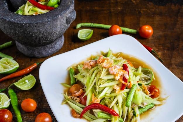 Thailändisches lebensmittel, papayasalat und papayasalat in einem teller mit einer umhüllung auf einem holztisch kochen.