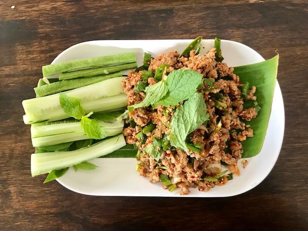 Thailändisches lebensmittel, würziger enten- und schweinefleischsalat auf weißer platte