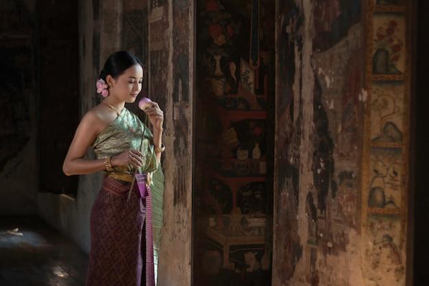 Thailändisches mädchen der schönheiten, das handlotos im traditionellen thailändischen kostüm mit tempel ayutthaya hält
