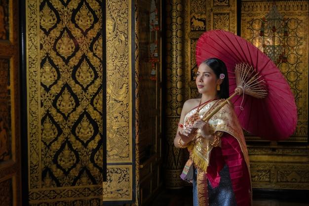 Thailändisches mädchen der schönheiten, das handlotos im traditionellen thailändischen kostüm mit tempel ayutthaya, identitätskultur von thailand hält.