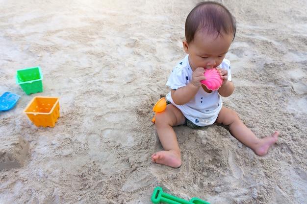 Thailändisches mädchen des asiatischen kleinkindbabys, das mit sand spielt