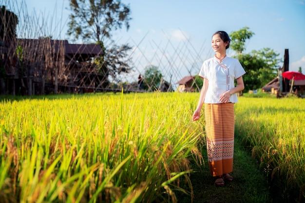Thailändisches mädchen gehen auf reis- und reisfarm in lamduan gewebtem stoffcafé