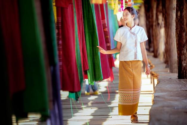 Thailändisches mädchen im traditionellen lanna-kostüm reisen in gewebtem lamduan-stoff