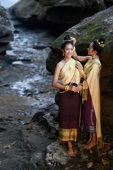 Thailändisches mädchen im traditionellen thailändischen kostüm in der wasserfallsteinschlucht, identitätskultur von thailand.
