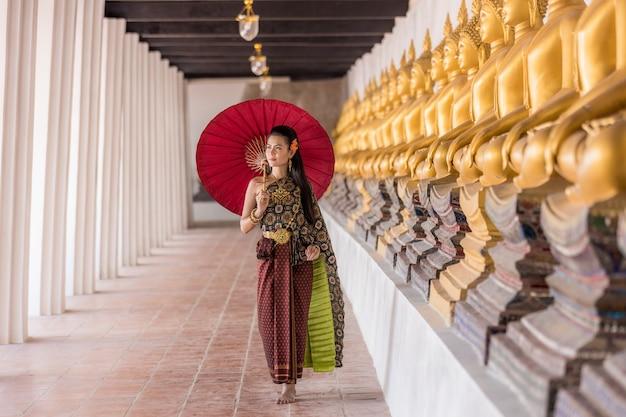 Thailändisches mädchen im traditionellen thailändischen kostüm mit rotem regenschirm im thailändischen tempel, identitätskultur von thailand.