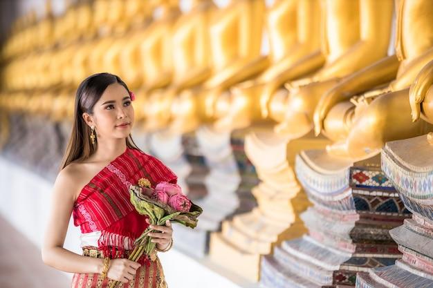 Thailändisches mädchen in der traditionellen thailändischen kostümhand, die lotos im thailändischen tempel, identitätskultur von thailand hält.