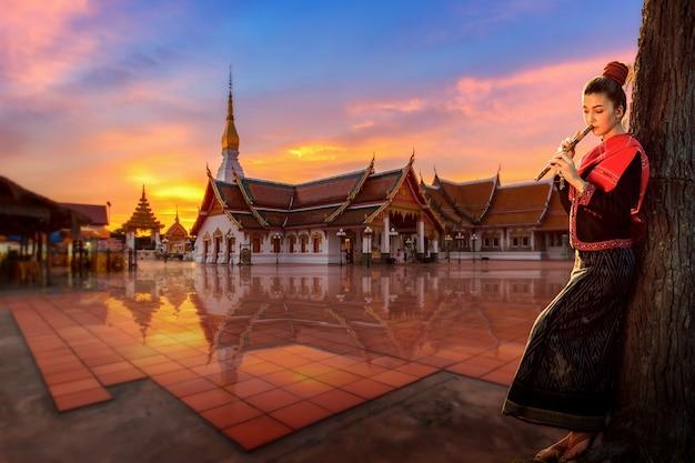 Thailändisches mädchen in einer nationaltracht, die zur thailändischen flöte im buddhistischen tempelbereich, sakonnakhon, thailand steht.