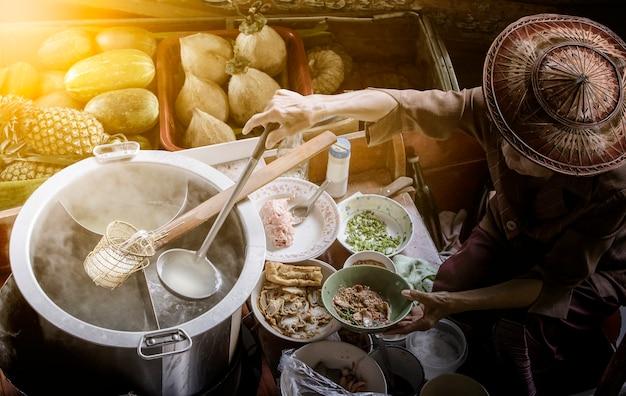 Thailändisches nudelfood, das auf sich hin- und herbewegendem boot in sich hin- und herbewegendem markt thailand macht