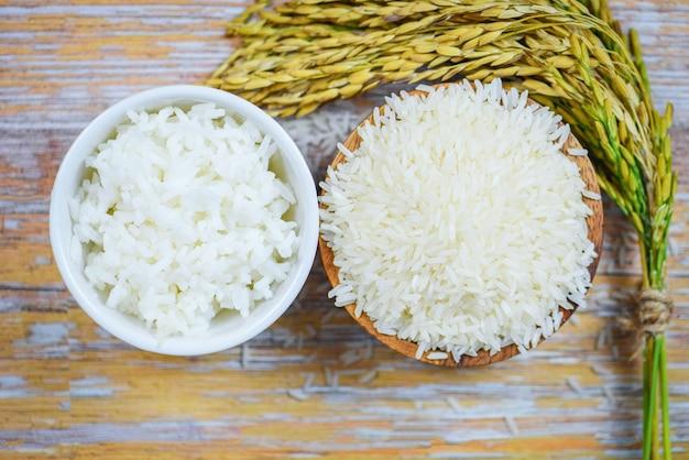 Thailändisches reisweiß auf hölzernem rohem und gekochtem jasminreiskorn der schüssel mit dem ohr von paddylandwirtschaftsprodukten für lebensmittel auf asiaten