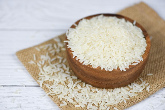 Thailändisches reisweiß auf schüssel- und sackhintergrund - rohe jasminreiskornlandwirtschaftsprodukte für lebensmittel auf asiaten