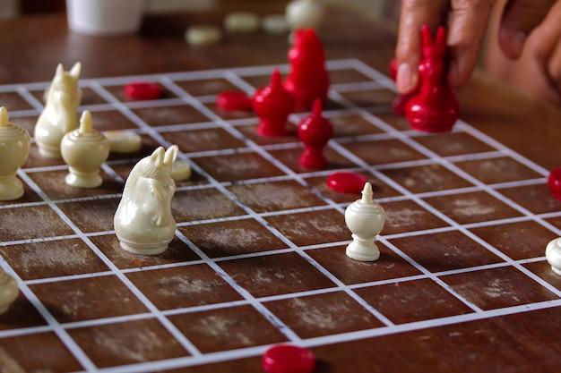 Thailändisches schachrennen im park. schach hat rot und weiß auf hölzernem schachbrett. brainspiele, hallensport