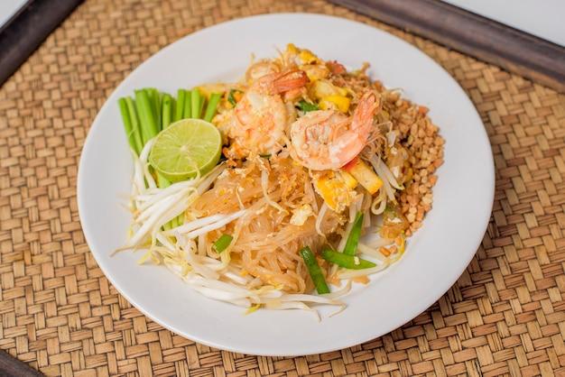 Thailändisches traditionelles essen pad thai nudeln mit garnelen in schüssel auf holztisch