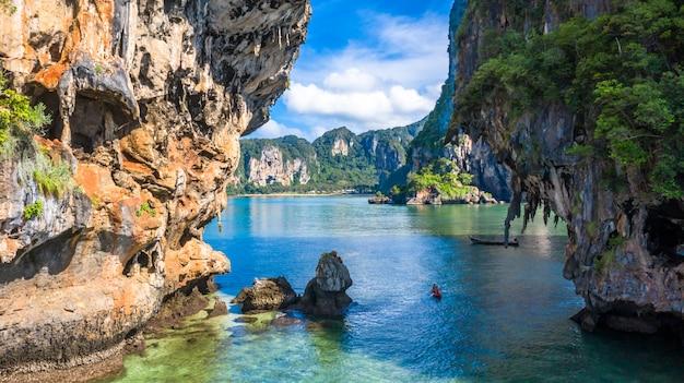 Thailändisches traditionelles hölzernes longtail-boot der vogelperspektive und schöner kalkstein