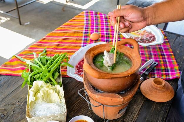Thailändisches traditionelles würziges shabu shabu des tongefäßes, fleisch in gekochte würzige suppe eintauchend.