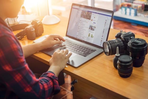 Thailand ein junger mann macht ein foto-shooting auf facebook, um online-produkte zu verkaufen.