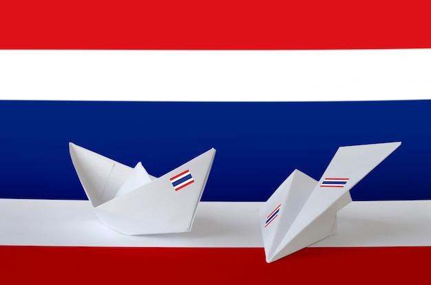 Thailand flagge dargestellt auf papier origami flugzeug und boot. handgemachtes kunstkonzept
