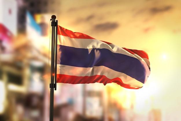 Thailand-flagge gegen stadt verschwommen hintergrund bei sonnenaufgang hintergrundbeleuchtung