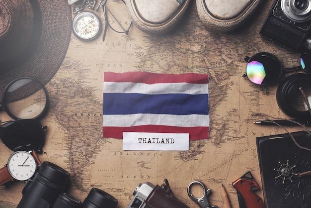 Thailand-flagge zwischen dem zubehör des reisenden auf alter weinlese-karte. obenliegender schuss