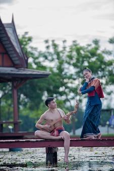 Thailand frauen und mann in tracht mit gitarrennadel (zupfinstrument)