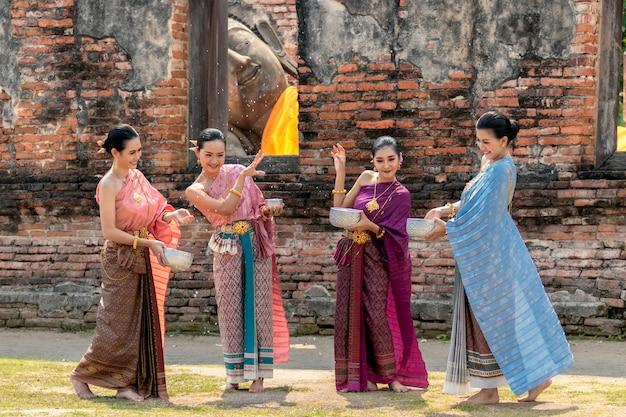 Thailand-kultur. thailändische mädchen und thailändische frauen, die spritzwasser während mit thailändischem traditionellem kostüm im tempel festival songkran ayutthaya thailand spielen.