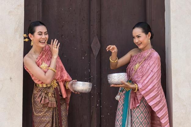 Thailand-kultur. thailändische mädchen und thailändische frauen, die spritzwasser während spielen.