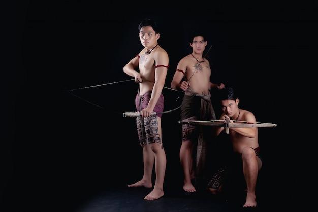 Thailand-mannkrieger, die in einer kämpfenden position mit waffen aufwerfen