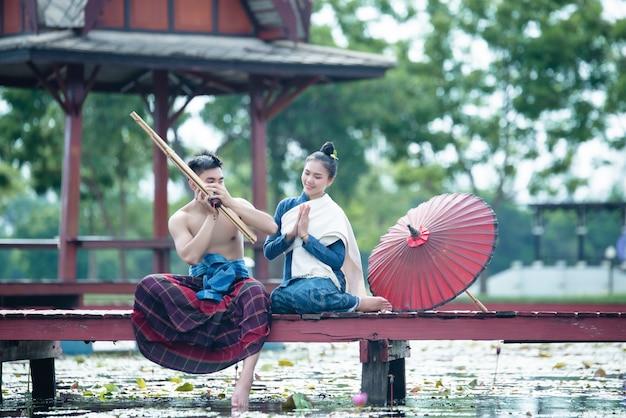 Thailand-musik, tanzenfrauen und mann im nationalen artkleiderkostüm: thailand-tanz