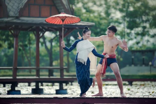 Thailand-tanzenfrauen und -mann im nationalen artkleiderkostüm: thailand-tanz