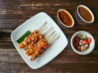 Thailändisches Essen, gegrilltes Schweinefleisch Satay mit Erdnusssoße und Essiggurken