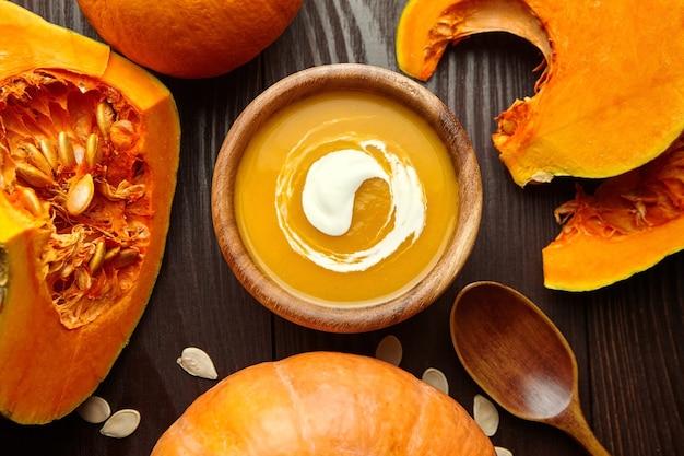 Thanksgiving-abendessen kürbiscremesuppe. kürbissuppe in der holzschale mit löffel auf tisch, draufsicht.