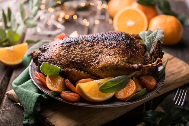 Thanksgiving-abendessen mit gebratener ente, dekoriert mit orange und kräutern.