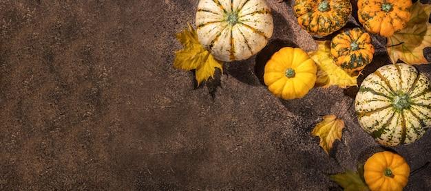 Thanksgiving day hintergrund, kürbisse und getrocknete herbstblätter auf braunem holztisch, herbstferien feiern, festivalkonzept, herbsternte