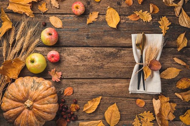 Thanksgiving day hintergrund mit herbstlaub kürbis äpfel und besteck auf einem hölzernen hintergrund