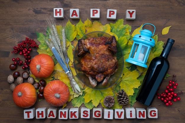 Thanksgiving day konzept mit gebackenem hühnchen und wein, kürbissen und herbstlaub