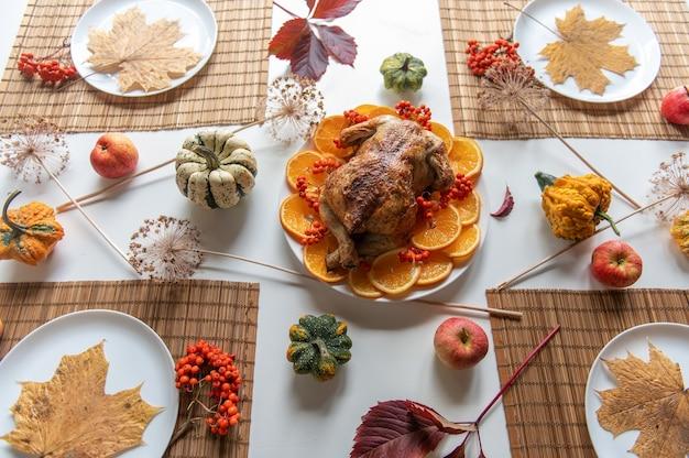 Thanksgiving-feier traditionelles abendessen einstellung essen konzept. draufsicht auf gebratenen truthahn auf einem gedeckten tisch.