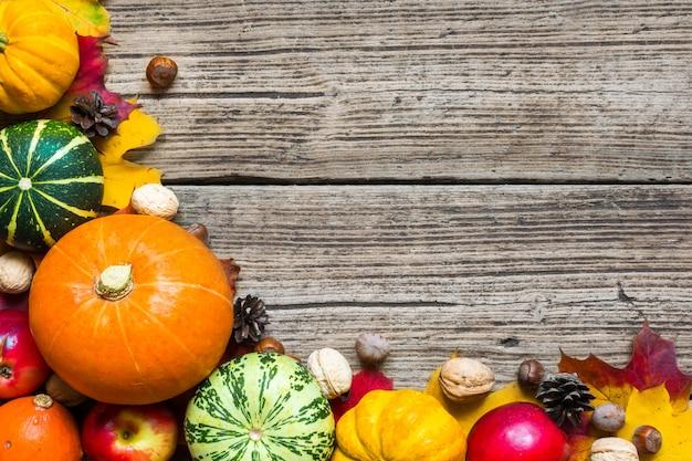 Thanksgiving-herbsthintergrund mit geernteten kürbissen, äpfeln, nüssen und ahornblättern