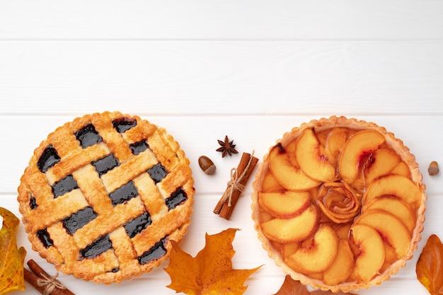 Thanksgiving-kuchen auf weißem holzbrett mit trockenen blättern und zimtstangen verziert