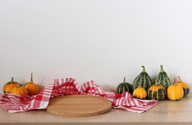 Thanksgiving-tisch mit kürbissen dekoriert, ein leeres schneidebrett und ein rot kariertes handtuch eine herbstliche halloween-kulisse