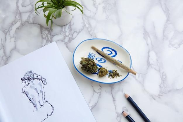 Thc cbd marihuana joint und blumen auf aschenbecher mit aktillustration auf zeichenblock