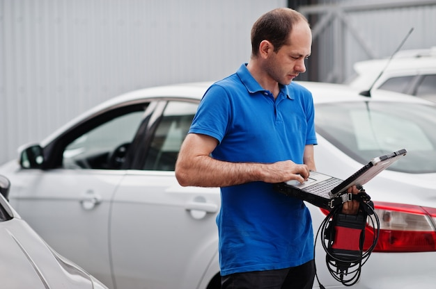 Thema autoreparatur und -wartung. elektromechaniker in uniform, der im autodienst arbeitet und autodiagnose unter verwendung des obd-geräts mit laptop macht.