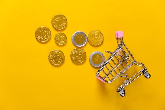 Thema einkaufen. mini-supermarktwagen mit münzen auf gelb.