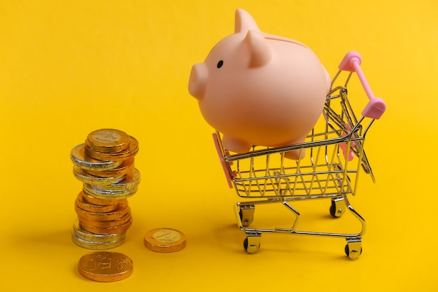 Thema einkaufen. mini-supermarktwagen mit sparschwein und münzen auf gelb.