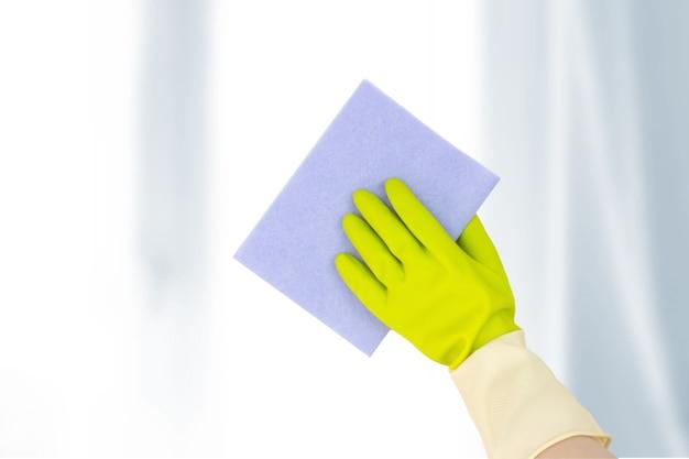 Thema fenster waschen. draufsicht der hand in gelben gummihandschuhen, die lappen halten und die fensteroberfläche abwischen. frühjahrsputz-konzept.