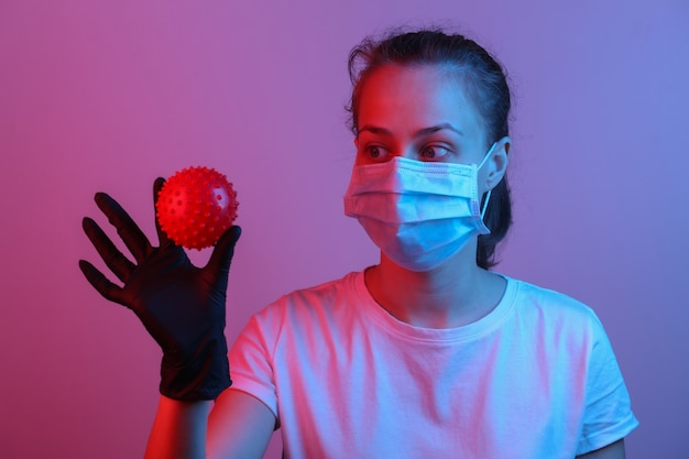 Thema pandemie covid-19. frau in schutzhandschuhen, medizinische gesichtsmaske hält ein virusstammmodell. rot-blaues neonlicht mit farbverlauf