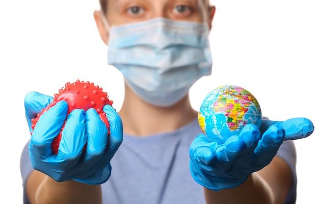 Thema pandemie covid-19. frau in schutzhandschuhen, medizinische gesichtsmaske hält ein virusstammmodell und einen auf weiß isolierten globus.