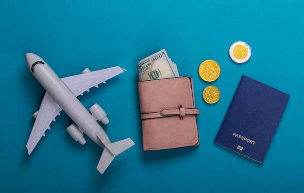 Thema reisen oder auswanderung. flugzeugfigur, geldbörse mit geld, reisepass auf blau